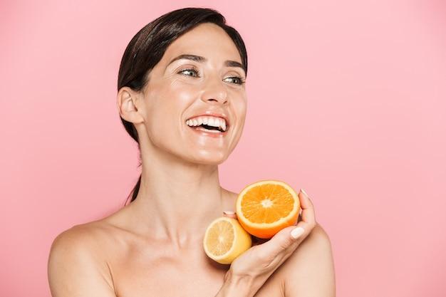 Schoonheidsportret van een aantrekkelijke glimlachende jonge topless vrouw die geïsoleerd staat over een roze muur, poserend met gesneden sinaasappel en citroen