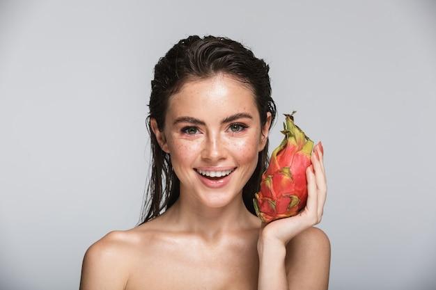 Schoonheidsportret van een aantrekkelijke glimlachende sensuele jonge vrouw met nat donkerbruin lang haar die zich geïsoleerd op grijs bevinden