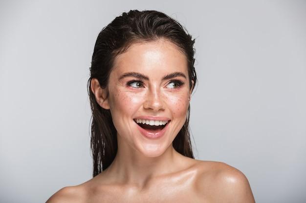 Schoonheidsportret van een aantrekkelijke glimlachende sensuele jonge vrouw met nat donkerbruin lang haar die zich op grijs geïsoleerd bevinden