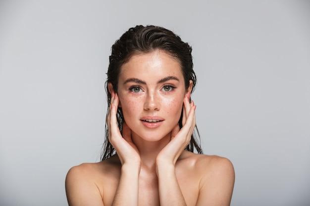 Schoonheidsportret van een aantrekkelijke glimlachende sensuele jonge vrouw met natte donkerbruine lange haren die geïsoleerd op grijs staan, haar gezicht aanraken, poseren