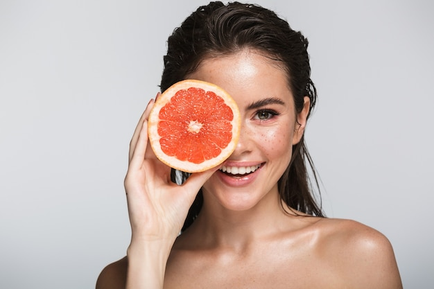 Schoonheidsportret van een aantrekkelijke glimlachende sensuele jonge vrouw met natte donkerbruine lange haren die geïsoleerd op grijs staan, met gehalveerde grapefruit, poserend