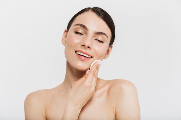 Schoonheidsportret van een aantrekkelijke jonge brunette vrouw die over een witte muur staat en de huid schoonmaakt met een wattenschijfje