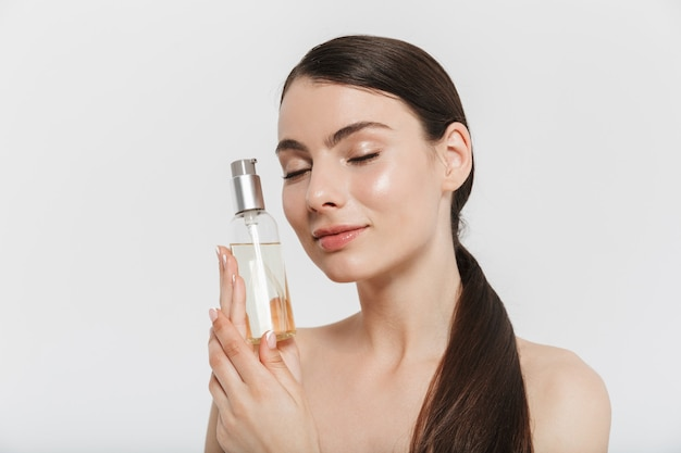 Schoonheidsportret van een aantrekkelijke jonge donkerbruine vrouw die zich geïsoleerd over witte muur bevindt, die fles met gezichtsolie toont