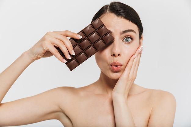 Schoonheidsportret van een aantrekkelijke jonge donkerbruine vrouw die zich geïsoleerd over witte muur bevindt, die zwarte chocoladereep toont