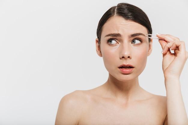 Schoonheidsportret van een aantrekkelijke jonge donkerbruine vrouw die zich geïsoleerd over witte muur bevindt, haar met pincet plukt