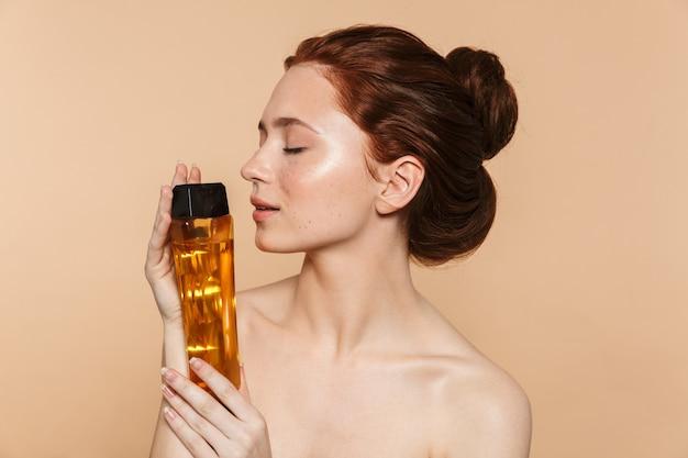 Schoonheidsportret van een aantrekkelijke jonge topless roodharige vrouw die geïsoleerd staat en een fles met cosmetische lotion toont
