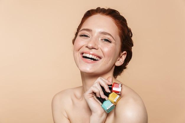 Schoonheidsportret van een aantrekkelijke jonge topless roodharige vrouw die geïsoleerd staat en nagellak toont