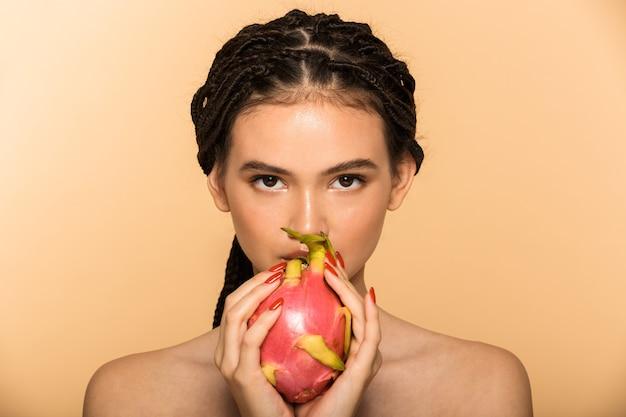 Schoonheidsportret van een aantrekkelijke jonge topless vrouw die geïsoleerd staat over een beige muur, poserend met drakenfruit