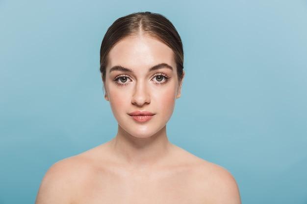 Schoonheidsportret van een aantrekkelijke jonge topless vrouw geïsoleerd over blauwe muur, poseren