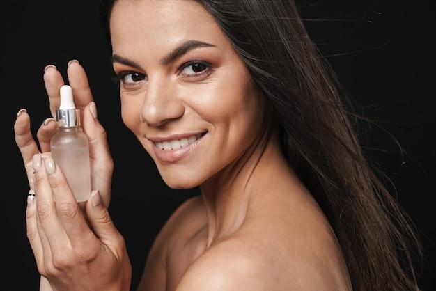 Schoonheidsportret van een aantrekkelijke jonge topless vrouw met lang donkerbruin haar geïsoleerd over zwarte muur, met make-up schoonheidsolie