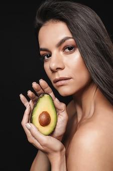Schoonheidsportret van een aantrekkelijke jonge topless vrouw met lang donkerbruin haar geïsoleerd over zwarte muur, poserend met gesneden avocado