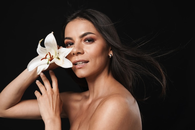 Schoonheidsportret van een aantrekkelijke jonge topless vrouw met lang donkerbruin haar geïsoleerd over zwarte muur, poserend met orchideebloem