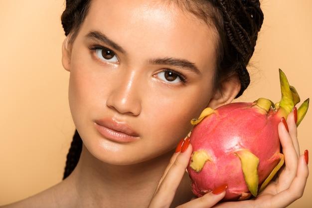 Schoonheidsportret van een aantrekkelijke jonge vrouw die geïsoleerd staat over een beige muur, poserend met drakenfruit
