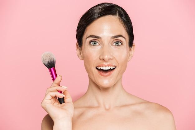 Schoonheidsportret van een aantrekkelijke opgewonden jonge topless vrouw die geïsoleerd over een roze muur staat en make-upborstel vasthoudt