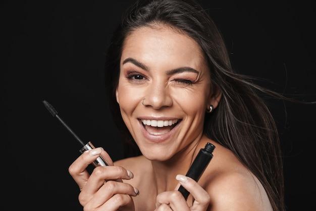 Schoonheidsportret van een aantrekkelijke opgewonden jonge topless vrouw met lang donkerbruin haar geïsoleerd over zwarte muur, met mascara