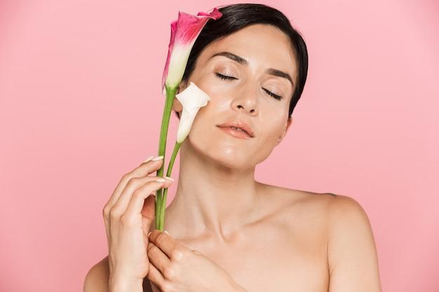 Schoonheidsportret van een aantrekkelijke sensuele gezonde topless brunette vrouw geïsoleerd over roze muur, poserend met irisbloem, ogen dicht