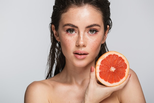 Schoonheidsportret van een aantrekkelijke sensuele jonge vrouw met nat donkerbruin lang haar geïsoleerd op grijs, met gehalveerde grapefruit, poserend
