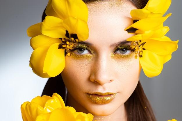 Schoonheidsportret van een brunette met uitgebreide wimpers in het beeld van een tulp. op een wit