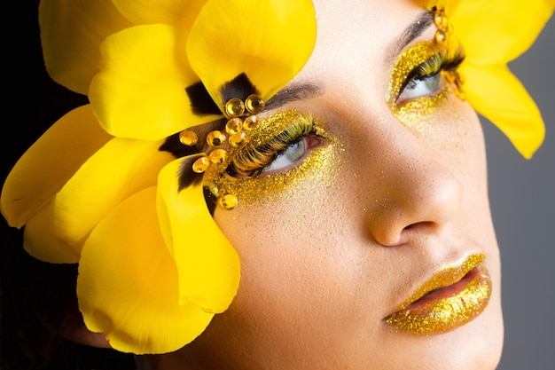 Schoonheidsportret van een brunette met uitgebreide wimpers in het beeld van een tulp.