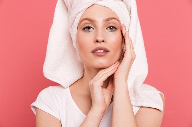 Schoonheidsportret van een charmante jonge vrouw gewikkeld in een witte handdoek na het douchen die haar schone, frisse gezicht aanraakt, geïsoleerd over roze muur