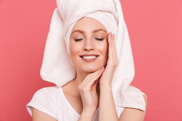 Schoonheidsportret van een elegante jonge vrouw gewikkeld in een witte handdoek na het douchen die haar schone, frisse gezicht aanraakt, geïsoleerd over roze muur