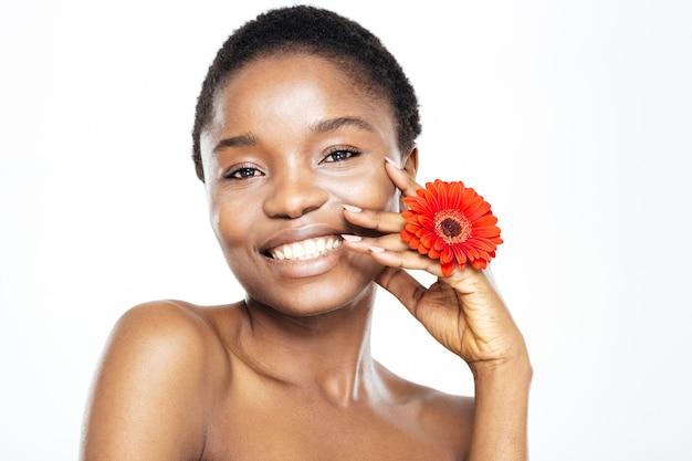 Schoonheidsportret van een gelukkige afro-amerikaanse vrouw met bloem die camera bekijkt die op een witte achtergrond wordt geïsoleerd