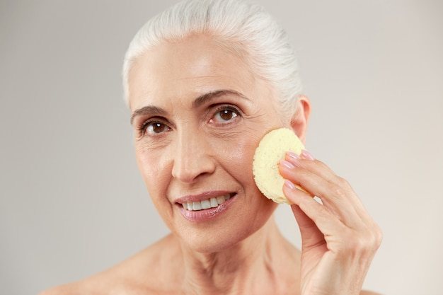 Schoonheidsportret van een glimlachende half naakte bejaarde die samenstellingsspons gebruiken bij haar gezicht en camera bekijken