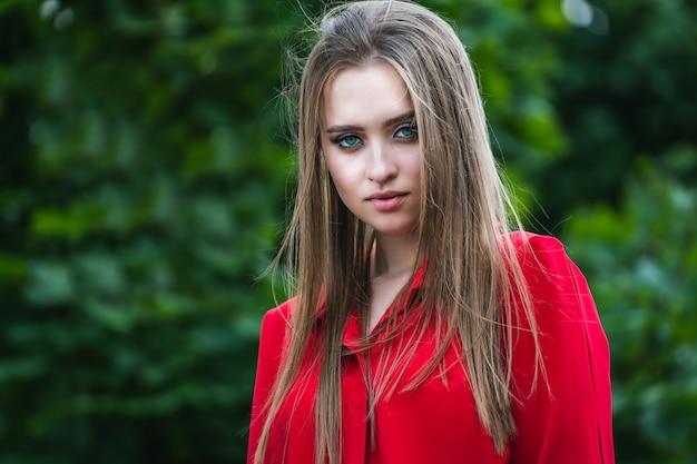 Schoonheidsportret van een jong mooi meisje met lang recht vliegend haar. prachtig haar. kleur portret. rode jurk.