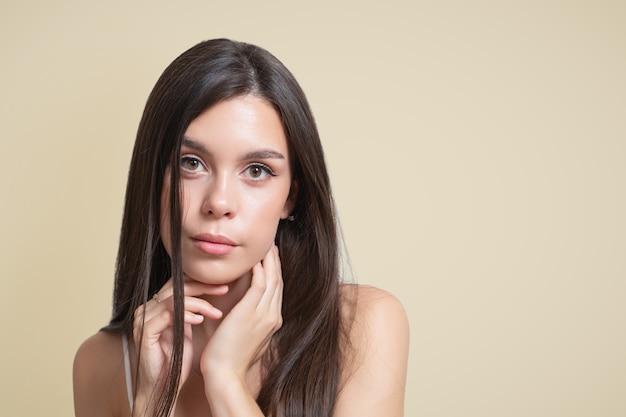 Schoonheidsportret van een jong vrouwenbruin meisje op een beige background