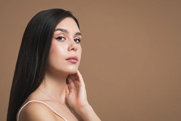 Schoonheidsportret van een jong vrouwenbruin meisje op een bruine achtergrond