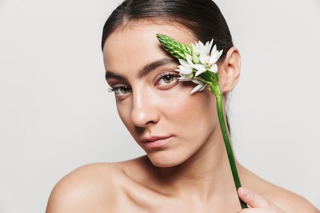 Schoonheidsportret van een jonge gezonde aantrekkelijke donkerbruine vrouw die geïsoleerd status, bloem op haar gezicht houdt