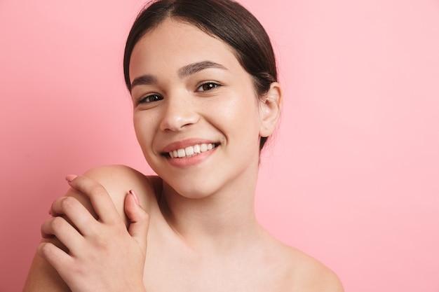 Schoonheidsportret van een lief lachend jong topless meisje dat geïsoleerd over een roze muur staat, poseren