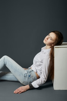 Schoonheidsportret van een mooi jong meisje op een donkere achtergrond. cosmetica voor tieners, acnebehandeling