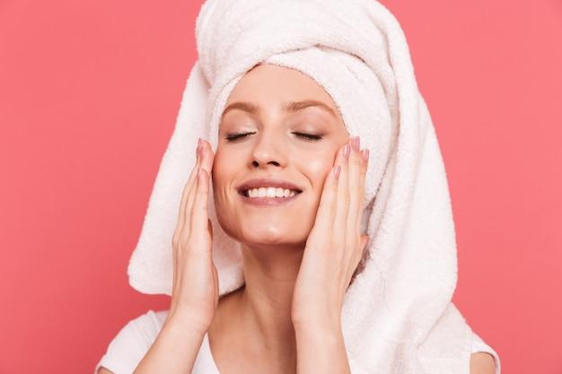 Schoonheidsportret van een prachtige jonge vrouw gewikkeld in een witte handdoek na het douchen die haar schone, frisse gezicht aanraakt, geïsoleerd over roze muur
