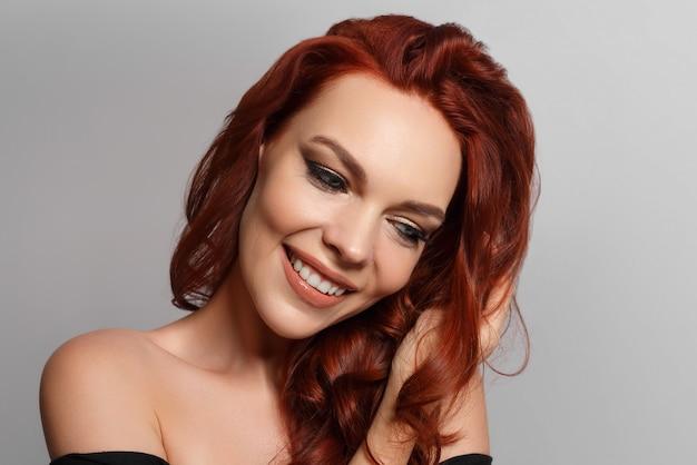 Schoonheidsportret van een roodharige gelukkige mooie vrouw op een grijze achtergrond.