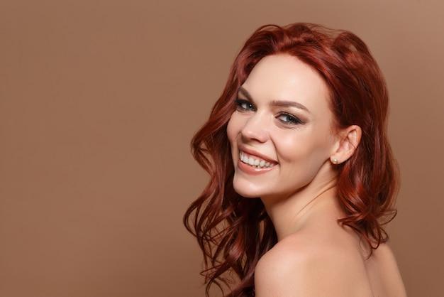 Schoonheidsportret van een roodharige mooie vrouw op een beige achtergrond. plaats voor copyspace.