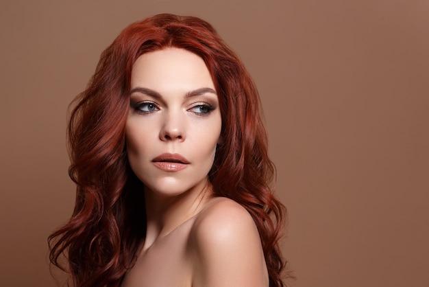 Schoonheidsportret van een roodharige mooie vrouw op een beige achtergrond..