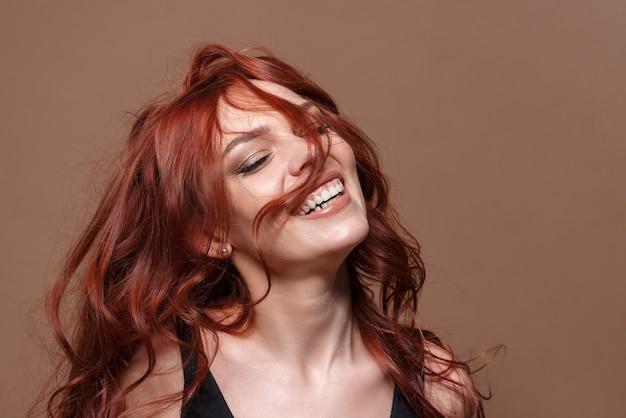 Schoonheidsportret van een roodharige mooie vrouw op een beige achtergrond