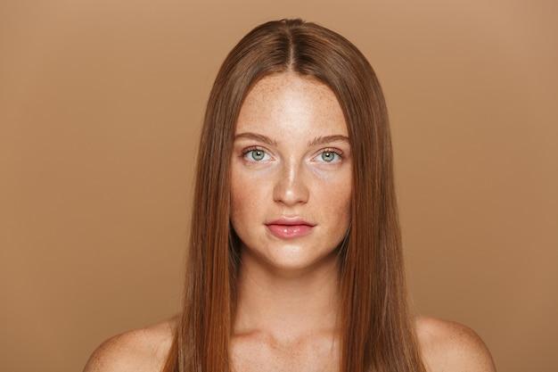 Schoonheidsportret van een sensuele jonge topless vrouw met lang rood haar dat over beige muur wordt geïsoleerd