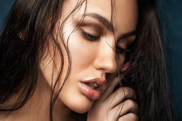 Schoonheidsportret van een verleidelijke vrouw. natte, stralende huid.