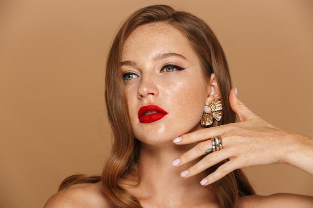Schoonheidsportret van een vrij jonge vrouw met lang rood haar die toebehoren dragen poseren geïsoleerd over beige muur