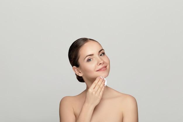 Schoonheidsportret van een vrolijke jonge topless vrouw die gezichtssamenstelling met een wattenschijfje verwijdert