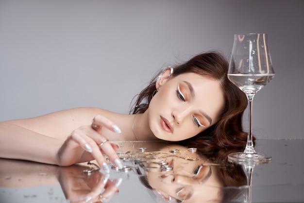 Schoonheidsportret van een vrouw met een in hand glas. de ringen liggen op de spiegeltafel. natuurlijke cosmetica