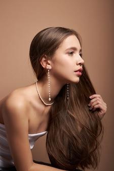 Schoonheidsportret van een vrouw met juwelen, oorringen in oren en halsband om hals. perfect schone gezichtshuid, natuurlijke cosmetica