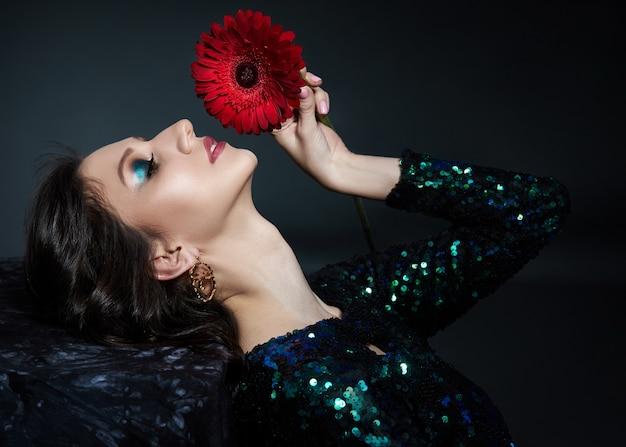 Schoonheidsportret van een vrouw met mooie avondmake-up en bloem