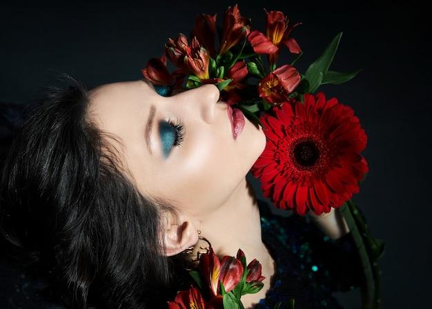 Schoonheidsportret van een vrouw met mooie avondmake-up en bloemen op haar gezicht, een brunette meisje in een glanzende avondjurk met pailletten. natuurlijke gezichtscosmetica, bloemblaadjes