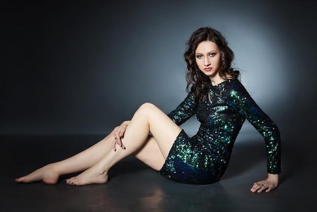 Schoonheidsportret van een vrouw met mooie avondmake-up zittend op de vloer, een brunette meisje in een glanzende avondjurk met pailletten. natuurlijke cosmetica voor gezicht