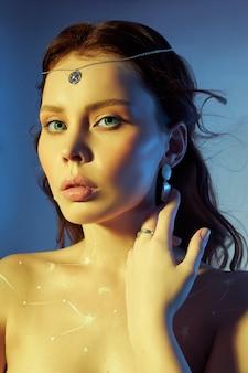 Schoonheidsportret van een vrouw met mooie make-up, oorbellen en een ketting op het meisje. kosmos-sterrenbeeld van de dierenriem tekenen op de borst van een vrouw