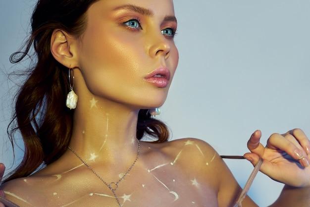 Schoonheidsportret van een vrouw met mooie make-up, oorringen en een halsband op het meisje