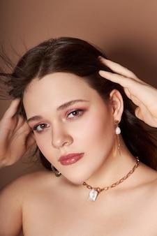 Schoonheidsportret van een vrouw met sieraden, oorbellen in haar oren en een ketting om haar nek. perfect schone gezichtshuid, natuurlijke cosmetica